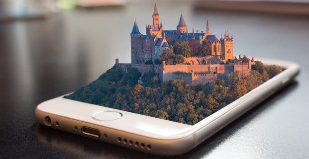 smartphone on table with 3D AR virtual reality castle surrounded by trees protruding from screen