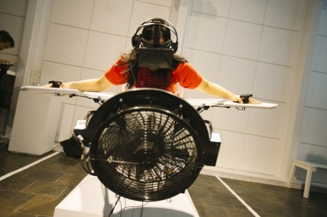 woman leaning forward with arms open wide wearing virtual realiy headset with fan blowing on her head Birdly VR experience
