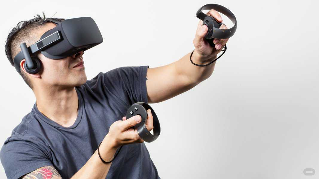 tattooed man with mohawk haircut in gray Tshirt wearing Oculus Touch VR headset holding controllers with thumb on buttons