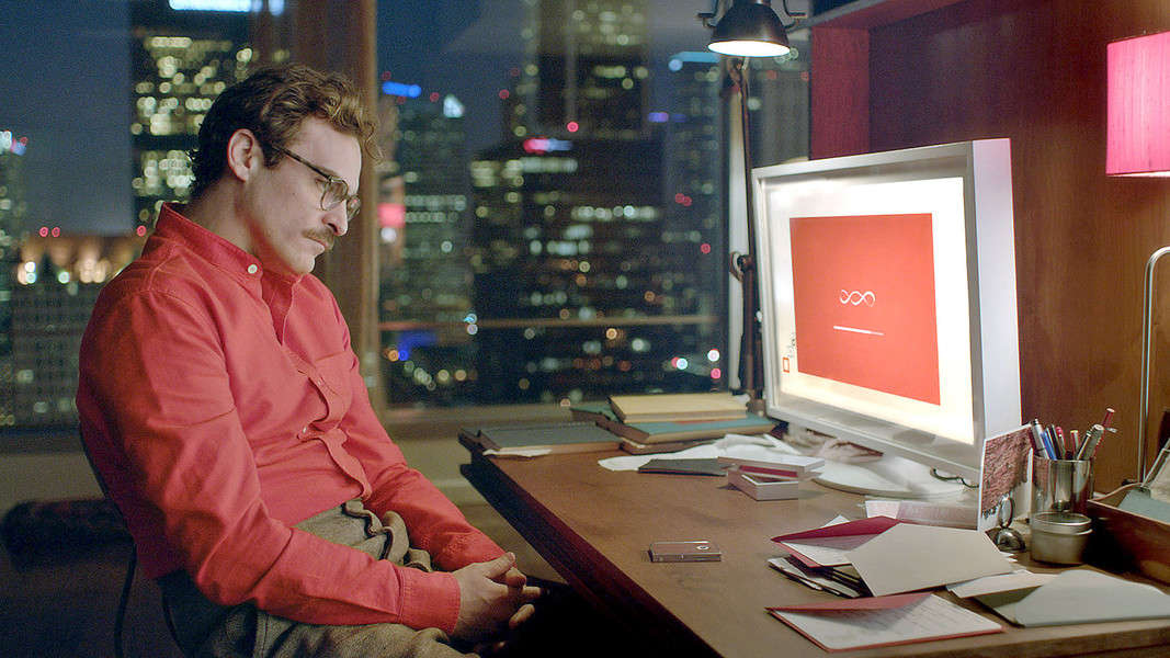 Joaquin Phoenix wearing glasses and a salmon-colored shirt sitting in front of a computer With Comp