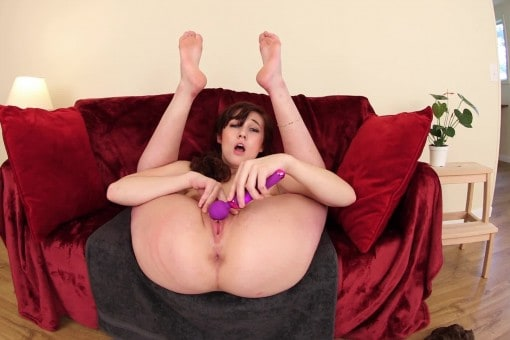 Curvy brunette on a red velvet couch masturbating with a pink dildo legs up in the air